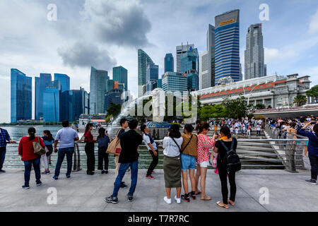 Tourists Taking Photos Of The Merlion Statue and Singapore Skyline, Singapore, South East Asia - Stock Photo