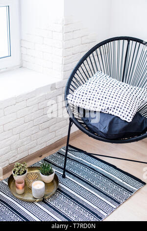 Bright white apartment interior decor, candles and plants on vintage tray with pillows in chair and carpet on the floor - Stock Photo