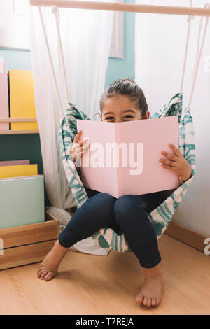 vertical photo of a sweet happy little girl reading a book in her room near the window, funny lovely child having fun in kids room - Stock Photo