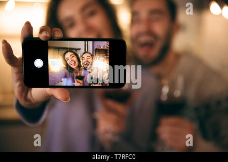 Beautiful happy young couple spending romantic evening together at home, drinking red wine, taking a selfie - Stock Photo