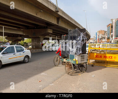 Street scene in Mahipalpur district, a suburb near Delhi Airport in New Delhi, capital city of India: typical overloaded delivery on an old tricycle - Stock Photo