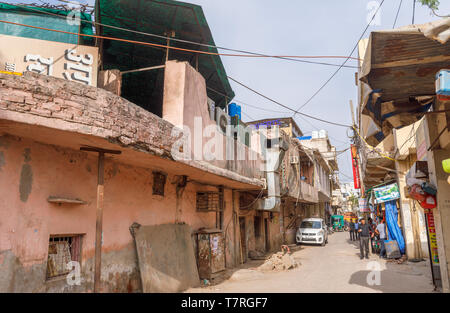 Street scene in Mahipalpur district, a suburb near Delhi Airport in New Delhi, capital city of India with typical dilapidated buildings - Stock Photo