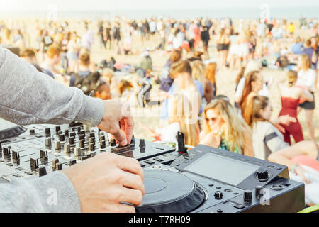Close up of DJ's hand playing music at turntable at beach party festival - Crowd people dancing and having fun in club outdoor - Stock Photo