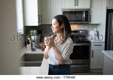 Thoughtful woman drinking coffee and looking out kitchen window - Stock Photo