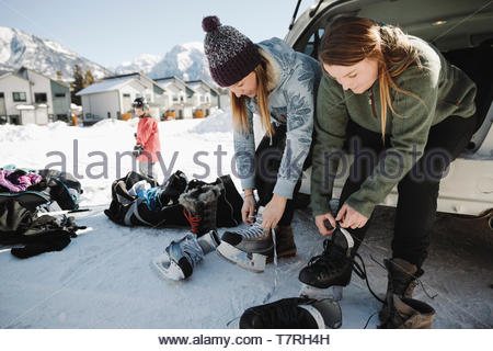 Women putting on ice skates at back of car - Stock Photo