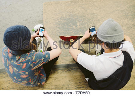 View from above teenage skateboarders using smart phones on ramp at indoor skate park - Stock Photo