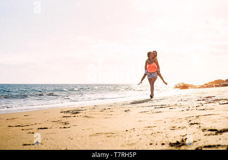Happy loving family mother and daughter running and having fun on the beach at sunset - Mom piggyback her kid next to ocean during holidays - Stock Photo