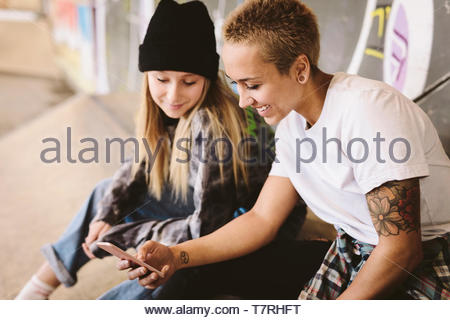 Young female skateboarders using smart phone at indoor skate park - Stock Photo