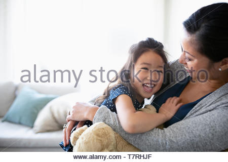 Happy, affectionate mother and daughter hugging - Stock Photo