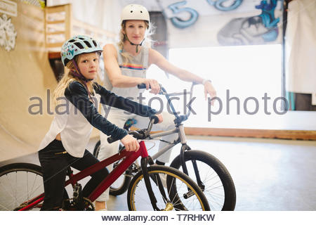 Portrait confident mother and daughter with bmx bikes at indoor skate park - Stock Photo