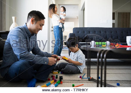 Father and son playing with plastic blocks in living room - Stock Photo
