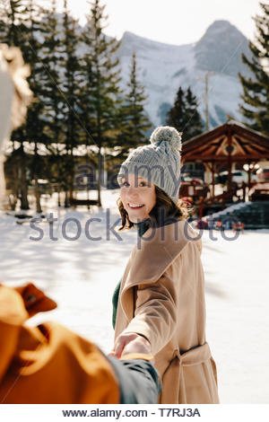 Smiling young woman holding boyfriend's hand in snow - Stock Photo