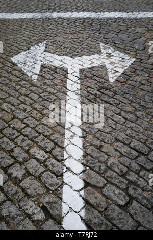 a painted arrow on a cobblestone road with left and right directions, concept. - Stock Photo