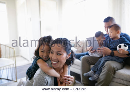 Happy family playing and using digital tablet in living room - Stock Photo