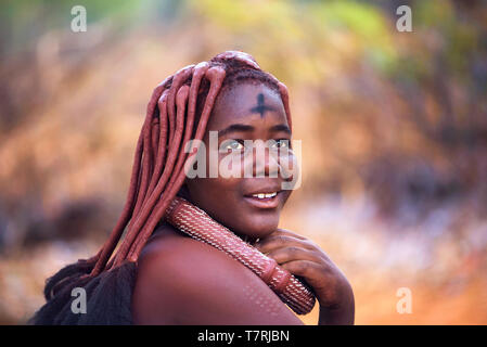 Beautiful and young himba tribe woman wearing traditional hairstyle and necklace - Stock Photo