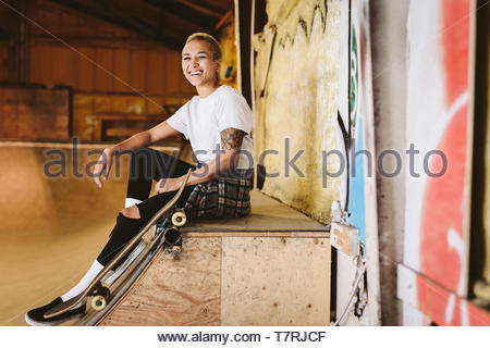 Portrait happy young female skateboarder sitting on ramp at indoor skate park - Stock Photo