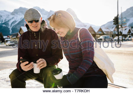 Senior couple using smart phone and drinking coffee on sunny, snowy bench - Stock Photo