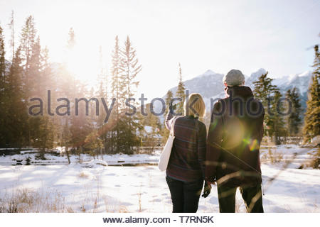 Senior couple looking at sunny, snowy mountain view - Stock Photo
