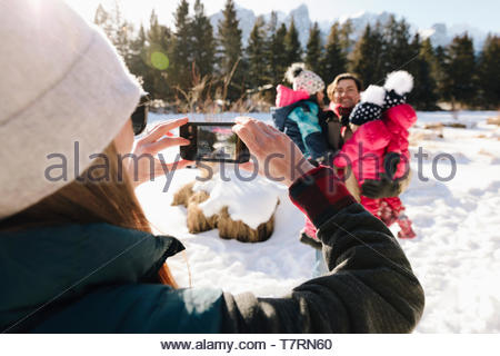 Woman with camera phone photographing family in snow - Stock Photo