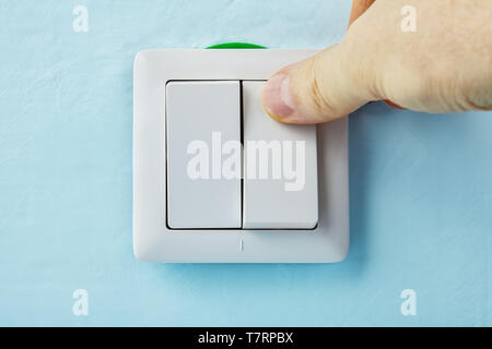 Repairman is pressing the button of new european standard  push button, electric installation work. - Stock Photo
