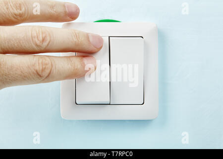 Electrician is pressing the button of new european standard  light switch, electrical installation. - Stock Photo