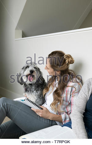 Woman with dog working from home - Stock Photo