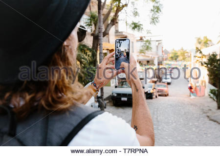 Young male tourist using camera phone on street, Mexico - Stock Photo