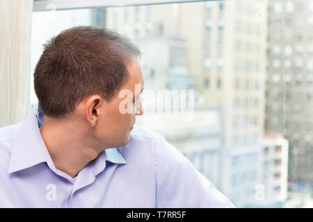 Young businessman closeup portrait sitting on windowsill in dress shirt looking at New York City cityscape skyline in Manhattan in hotel for interview - Stock Photo