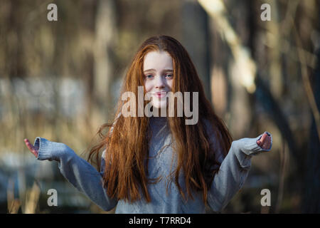 Cute teengirl with fiery red hair in the pine park. The girl was surprised, threw up his hands. - Stock Photo
