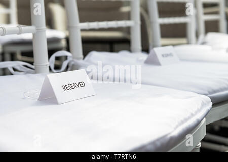 White wedding chairs with reserved signs closeup for ceremony with background of rows of many seats and nobody - Stock Photo