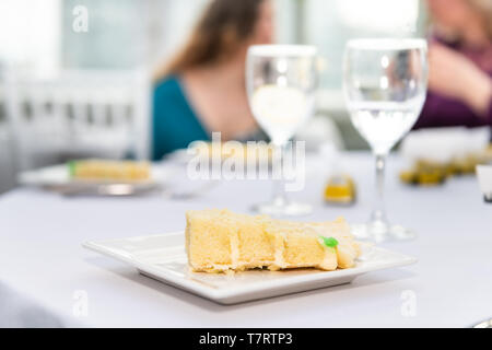 Table with glasses of water in restaurant or wedding reception white table tablecloth plates with yellow cake slices and background of guests eating - Stock Photo