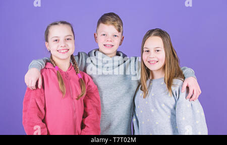 Real friendship. friends children embrace. childhood friendship. family bonds. team work concept. having fun together. support. little girls sister and boy. sportswear fashion. happy childrens day. - Stock Photo
