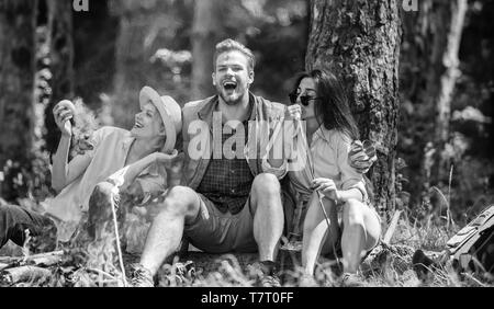 Company friends relaxing and having snack picnic nature background. Halt for snack during hiking. Company hikers relaxing at picnic forest background. Camping and hiking. Relax and fun in nature. - Stock Photo