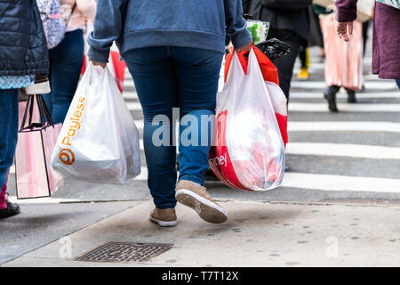 New York City, USA - April 6, 2018: Manhattan NYC sidewalk in midtown on 6th avenue road and closeup of people walking woman carrying Payless and JCPe - Stock Photo