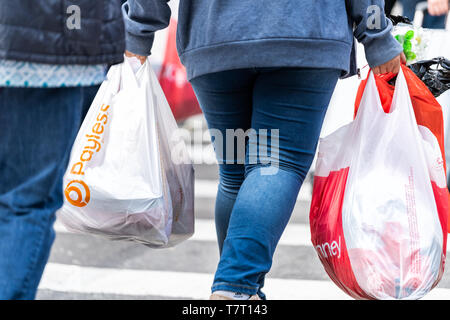 New York City, USA - April 6, 2018: Manhattan NYC sidewalk in midtown on 6th avenue road and closeup of people legs walking woman carrying Payless and - Stock Photo