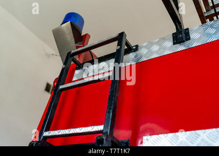 Blue warning signal placed on the back of the fire truck, visible  ladders. - Stock Photo