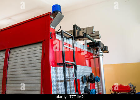 Blue warning signal placed on the back of the fire truck, visible water valves and ladders. - Stock Photo