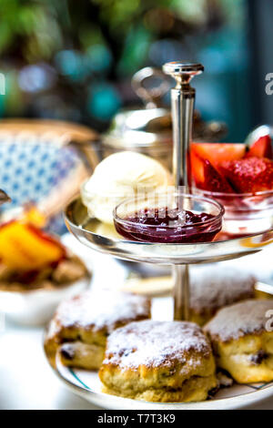 Scones, jam and clotted cream on a tiered tray, afternoon tea at Ivy in the Park in Canary Wharf, London, UK - Stock Photo