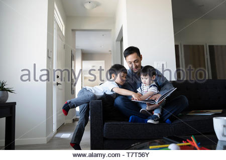 Father and toddler children reading book on living room sofa - Stock Photo