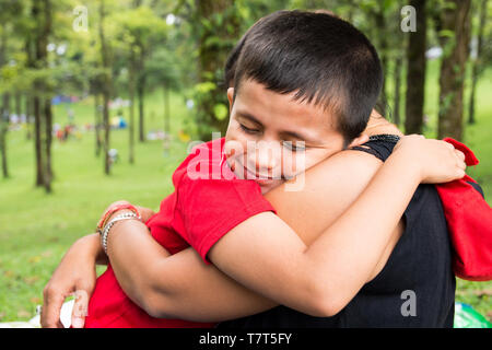 young boy hugging his mother in the park with closed eyes and smiling, happy and tender childhood/parenting moment. - Stock Photo