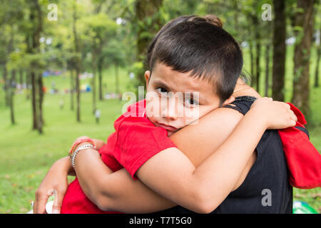 8 year old boy hugging his mother in the park and looking at camera with emotional expression on his face - Stock Photo