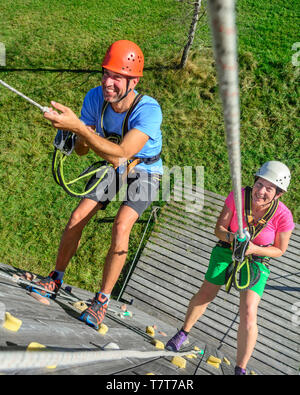 Two adults during an abseiling exercise in high ropes park - Stock Photo