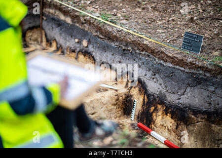 Bielefeld, Germany. 08th May, 2019. A trainee excavation technician sits at the excavation site where the exposed base layer of the Roman marble can be seen. Archaeologists of the Landschaftsverband Westfalen-Lippe (LWL) have uncovered the remains of a 2000 year old Roman marsh marsher in the district of Sennestadt. Credit: Guido Kirchner/dpa/Alamy Live News - Stock Photo