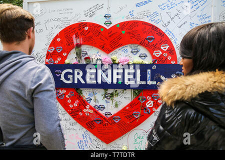 June 14, 2018 - London, United Kingdom - People seen looking at a Grenfell placard..On 14 June 2017, a fire broke out in the 24-storey Grenfell Tower block of flats in North Kensington, West London where 72 people died, more than 70 others were injured and 223 people escaped..The UK Government is to fund an estimated £200 million to replacement of unsafe Grenfell style cladding on around 170 high-rise private residential buildings after private building owners failed to take action. Communities Secretary James Brokenshire said inaction from building owners had compelled the government to act. - Stock Photo