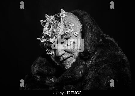 Alien, demon, sorcerer makeup. Horror and fantasy concept. Man with thorns or warts in fur coat. Demon on black background, copy space. Senior man - Stock Photo