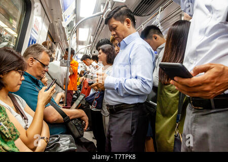 People Looking At Their Smartphones On The MRT, Singapore, South East Asia - Stock Photo