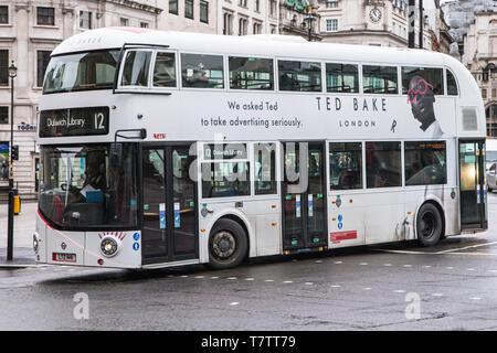 London, United Kingdom - December 23, 2019: Wrightbus New Routemaster in white livery travelling around Trafalgar Square heading towards Dulwich Libra - Stock Photo