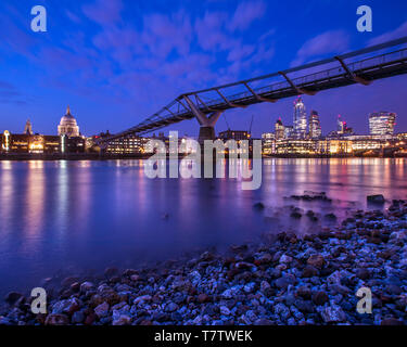 A view of the magnificent St. Pauls Cathedral and the Millennium Bridge spanning over the River Thames in London, UK. The modern skyscrapers in the Ci - Stock Photo