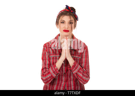 Head shot studio portrait millennial woman pose over white background looking at camera cupped hands in praying gesture feels sad desperate, symbol of - Stock Photo