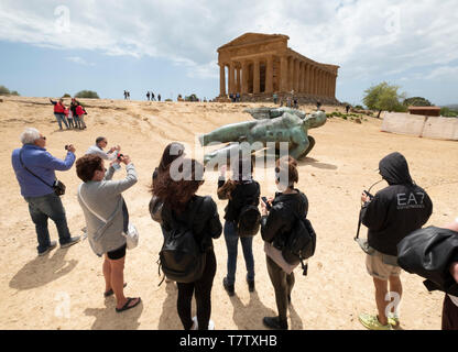 Temple of Concordia & Fallen Ikarus sculpture by Igor Mitoraj, Valley of the Temples, Agrigento. Sicily. Italy - Stock Photo